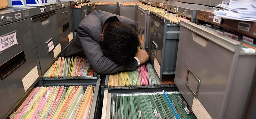 office worker burdened by file cabinets